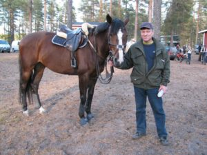 Ari seisoo pidellen Cara hevosen suitsista kiinni.